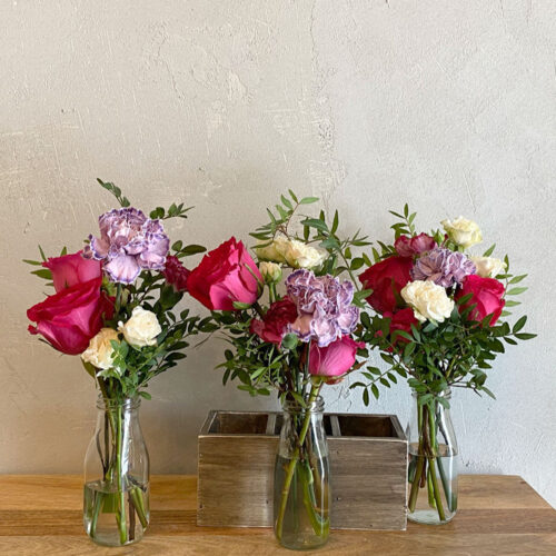A trio of Carnation's & Roses in bottles